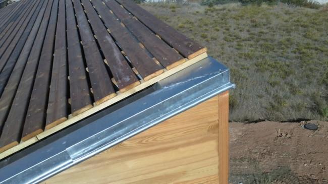 Couverture en bac acier avec sur-toiture en planches et rives en zinc